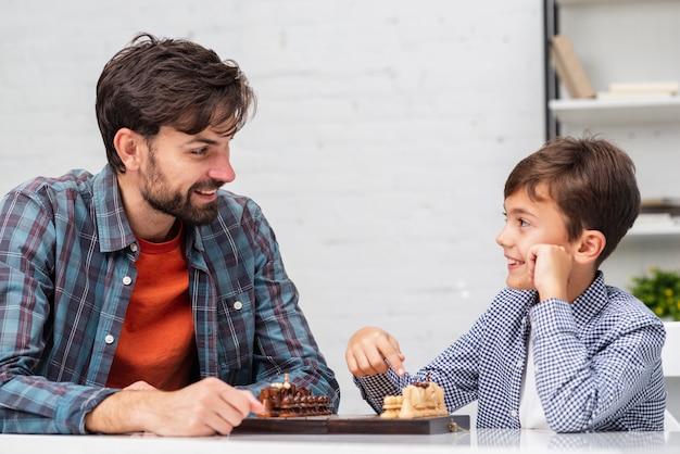 Отец и сын играют в шахматы и смотрят друг на друга