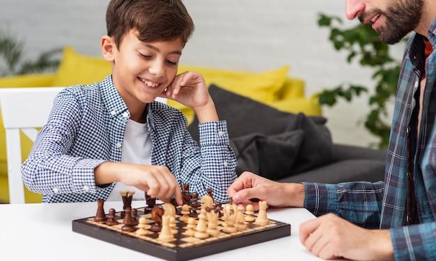 Счастливый сын играет в шахматы со своим отцом