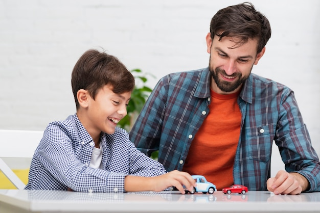 Папа и сын играют с игрушечными машинками