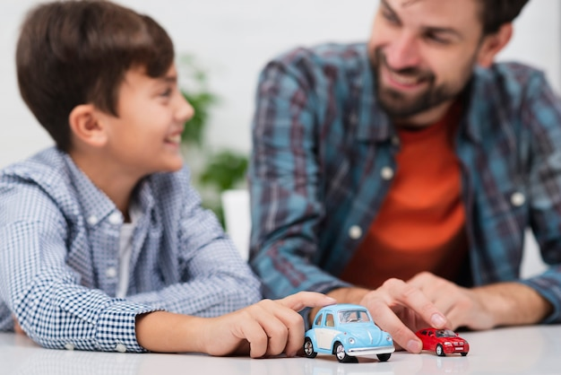 Отец и сын играют в игрушечные машинки и смотрят друг на друга