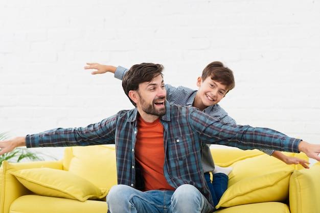 Забавный отец и сын играют на диване