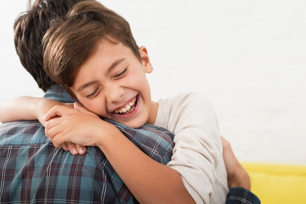 彼の父を抱きしめる幸せな少年