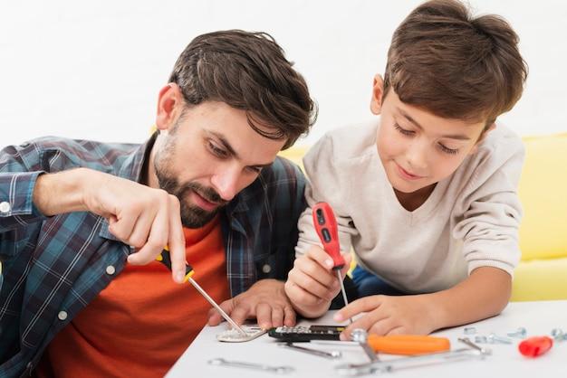 Отец и сын чинят игрушечные машинки