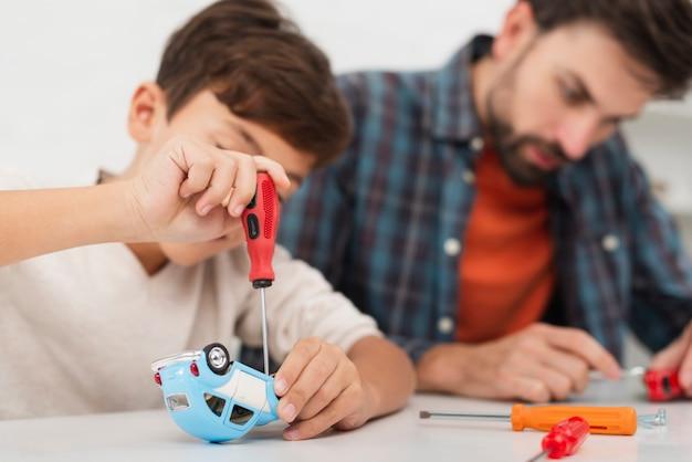 息子と父親のおもちゃの車を修正