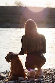 Вид сзади молодая женщина со своей собакой