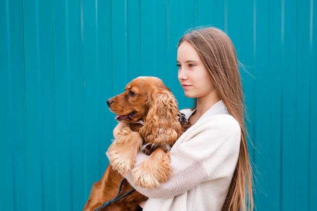 彼女のかわいい犬を保持している若い女性