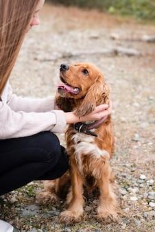 Женщина гладит очаровательную собаку