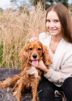 スマイリー女性が彼女の子犬とポーズ