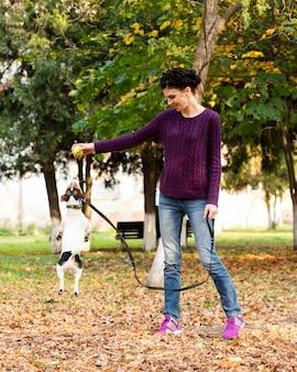 彼女の犬と遊ぶフルショット女性