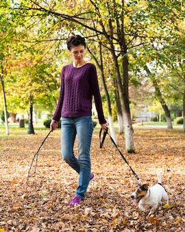 公園で彼女の犬を持つ若い女性の肖像画