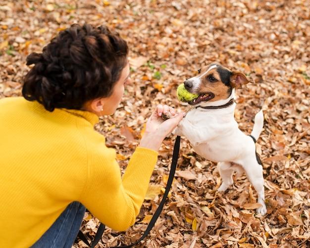 彼女の子犬と遊ぶクローズアップ女性