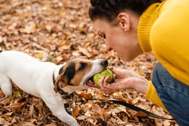 Крупным планом женщина играет со своей собакой