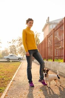 Полный выстрел женщина со своей собакой на открытом воздухе