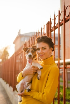 彼女の犬を保持している幸せな若い女