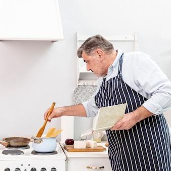Старший мужчина готовит с деревянной ложкой