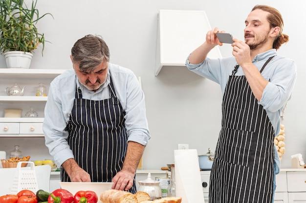 息子が父親の料理の写真を撮る