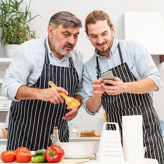 スタイリッシュな父と息子が電話で見ています