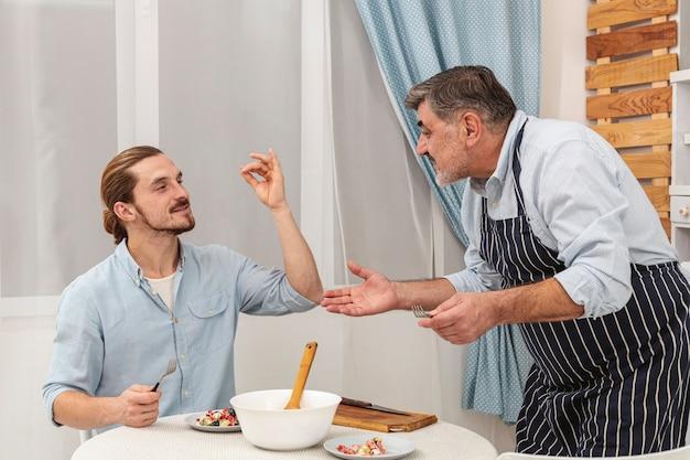 Счастливый отец и сын подают ужин