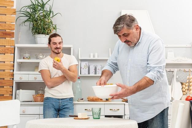 夕食の準備の父を見ている息子