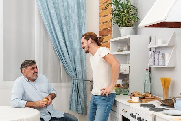 ミディアムショットの父と息子が台所で話しています。