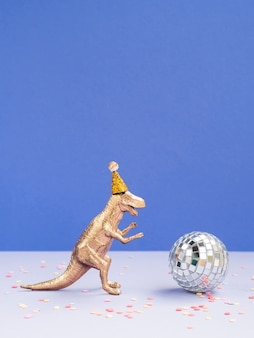 Забавный динозавр с шляпой на день рождения и диско-шаром