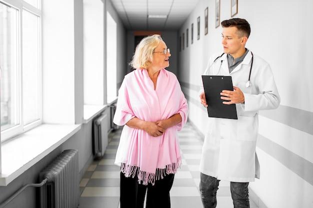 医師と病院のホールを歩く女性