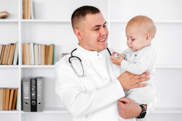 素敵な赤ちゃんを保持している慎重な医者
