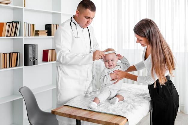 Доктор измеряет голову новорожденного