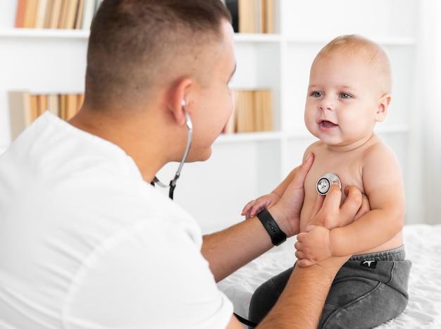 Доктор слушает маленького ребенка со стетоскопом