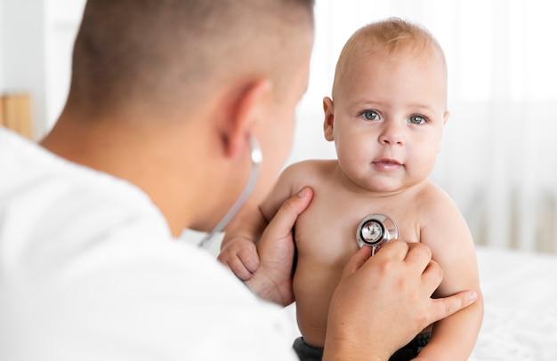 聴診器で小さな赤ちゃんを聞いて背面ビュー医師