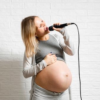 Смешная беременная женщина поет