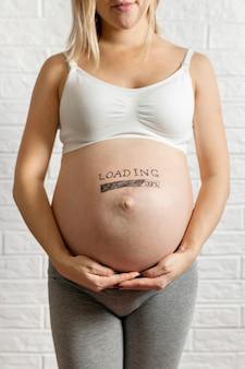 Вид спереди беременной женщины, держащей ее живот