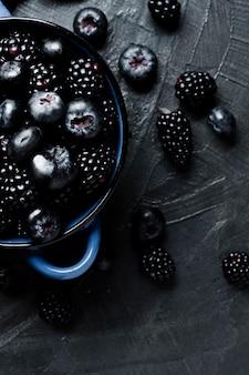 フラットポットに黒い森の果物を置く