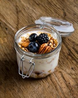 Высокий угол йогурта с лесными фруктами и орехами