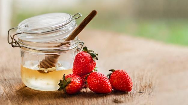 蜂蜜の瓶の近くの正面イチゴ