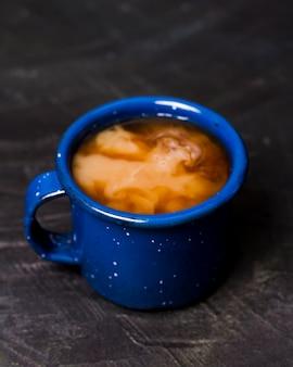 青いマグカップでミルク入りのコーヒー