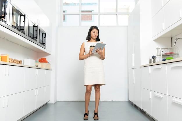キッチンでタブレットで働く女性