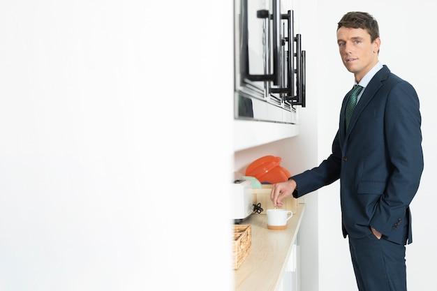 一杯のコーヒーとオフィスでスーツでポーズの男