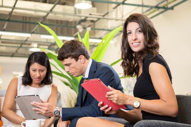 Женщина позирует с планшетом в офисе
