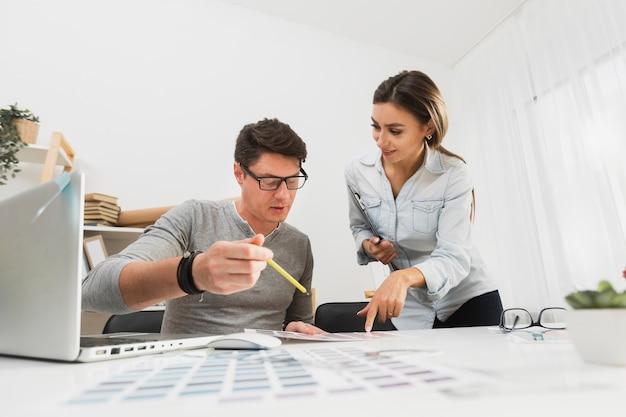 Вид спереди мужчина и женщина, работающая на деловых бумагах