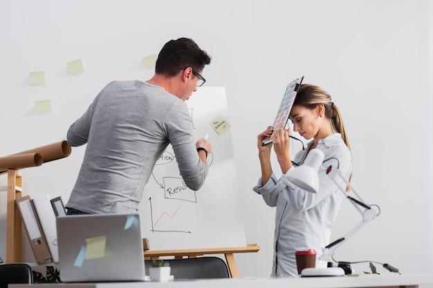 女性の同僚に図を説明しようとしている男