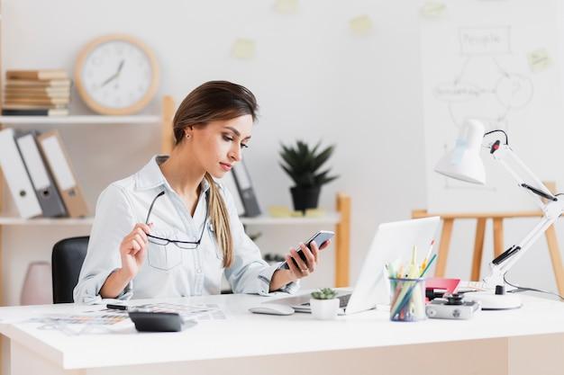 Бизнес женщина держит ее очки и смотрит на телефон
