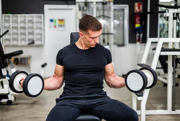 Человек высокого угла на тренировке спортзала с весами