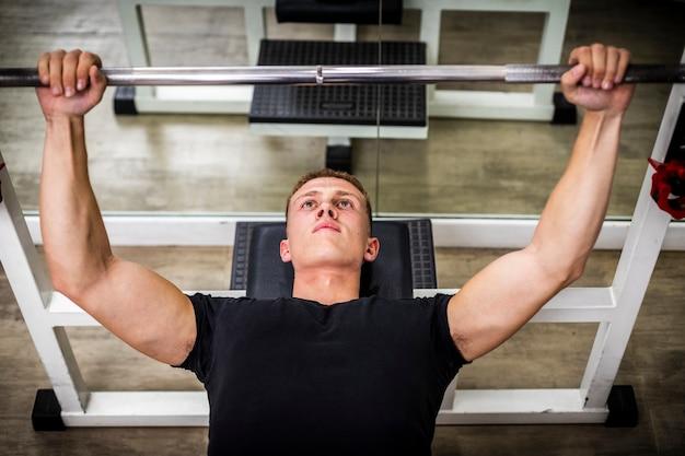 Молодой человек, поднятие тяжестей в тренажерном зале