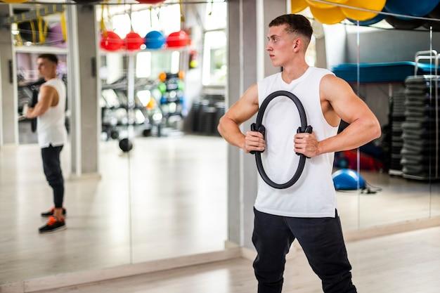 Молодой человек на тренировке тела смотря в зеркало