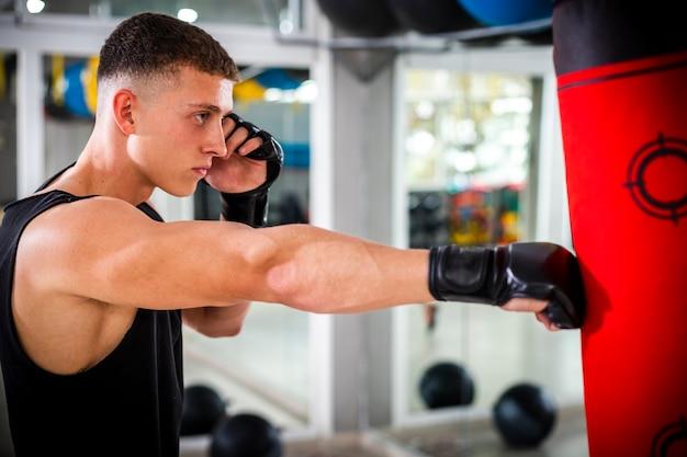 Тренировка человека с боксерской грушей