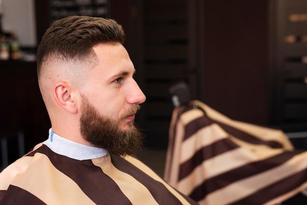 彼のひげを手入れするのを待っている男