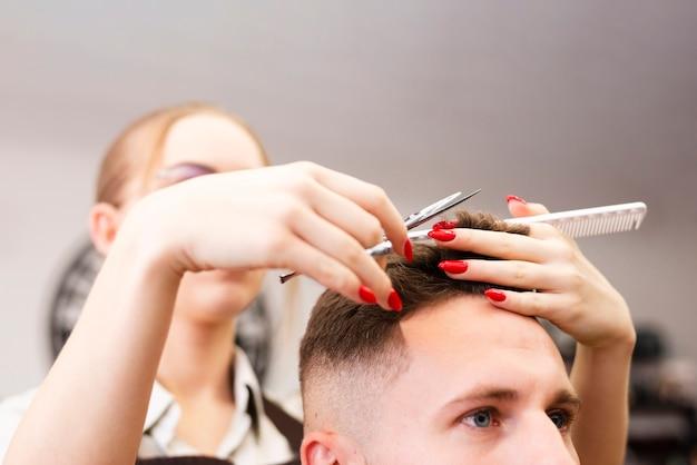彼女の仕事のクローズアップを行うプロの理髪店の労働者