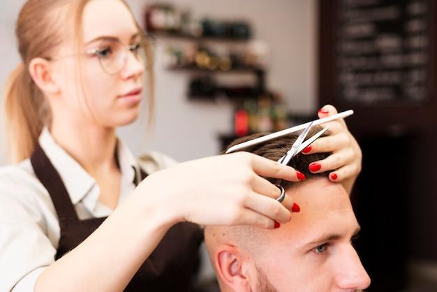 彼女の仕事をしているプロの理髪店の労働者