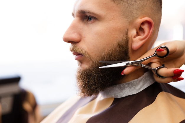 プロの理髪店で男のひげを切る女性